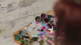 Конец-вверх художника девушки моет щетку для того чтобы покрасить в воде взгляд сверху сток-видео