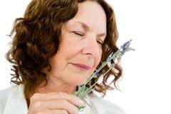 Конец-вверх цветков зрелой женщины пахнуть Стоковые Фото