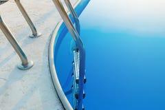 Конец-вверх части бассейна с лестницей нержавеющей стали и открытого моря на заходе солнца Летние каникулы, праздники, ослабляют стоковое фото