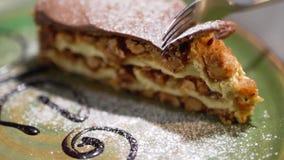 Конец-вверх части очень вкусного торта лежа на плите Вилка режет часть вкусного пирога торта с гайками движение медленное сток-видео