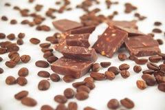 конец вверх части шоколада и кофейных зерен изолированных на белизне Фото с космосом экземпляра Стоковое Изображение