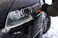 Конец-вверх человека, очищает headlamp от снега Стоковое Изображение