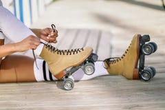 Конец-вверх черной девушки сидя на деревянном поле кладет дальше коньки Стоковое Изображение RF