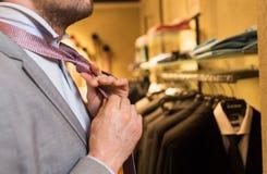 Конец вверх человека связывая связь на зеркале магазина одежды стоковое изображение