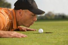 Конец-вверх человека дуя на шаре для игры в гольф Стоковые Изображения RF