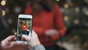 Конец-вверх человека фотографируя его привлекательная девушка outdoors Гай используя его мобильное устройство для фотографировать видеоматериал