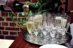 Конец-вверх шампанского спирта сильной руки ` s кельнера лить стоковые изображения rf
