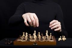 Конец-вверх шахматной доски и деревянных диаграмм шахмат и руки o Стоковая Фотография