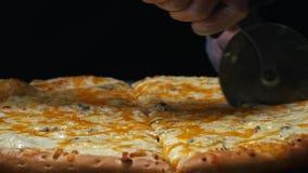 Конец-вверх шеф-повара в белых перчатках режа очень вкусную пиццу сыра 4 на деревянной доске на таблице r Традиционный акции видеоматериалы