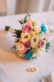 Конец-вверх bridal букета с обручальными кольцами пар золотыми Стоковые Фотографии RF