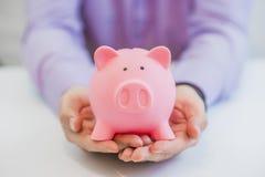 Конец-вверх Businessman& x27; рука s держа Piggybank над белой предпосылкой Стоковые Фото