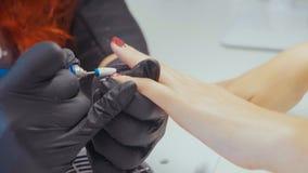 Конец-вверх manicurist извлекая старый гель полирует используя elecrtric пилочку для ногтей Стоковая Фотография RF