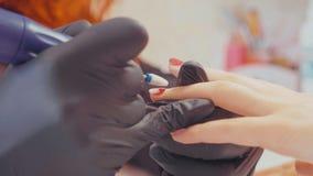 Конец-вверх manicurist извлекая старый гель полирует используя elecrtric пилочку для ногтей Стоковые Фотографии RF