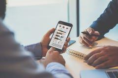 Конец-вверх smartphone с диаграммами, диаграммами и диаграммами на экране в руках бизнесмена, сидя на таблице Стоковое Изображение RF