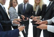 Конец-вверх smartphones в руках молодости дела Стоковое Изображение
