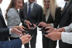 Конец-вверх smartphones в руках молодости дела Стоковые Фото
