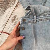 Конец-вверх sundress джинсовой ткани на деревянной предпосылке стоковое фото