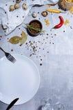 Конец-вверх tableware рядом с деревянным шаром приправы Яичка триперсток и яркие перцы chili на серой предпосылке Стоковое фото RF
