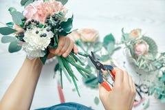 Конец взгляда сверху вверх по женскому положению цветков отрезков на счетчике Аранжировать различные цветки в современном свежем  стоковое изображение