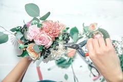 Конец взгляда сверху вверх по женскому положению цветков отрезков на счетчике Аранжировать различные цветки в современном свежем  стоковая фотография rf
