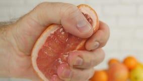 Конец грейпфрута вверх по изображению с половиной отжимать руки плода и сжимать сок стоковые изображения rf