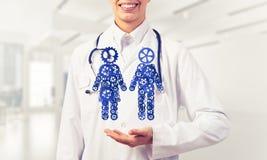 Конец женского работника медицины показывая в figu пар шестерни ладони Стоковое Изображение