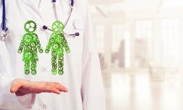 Конец женского работника медицины показывая в figu пар шестерни ладони Стоковая Фотография