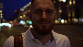 Конец замедленного движения вверх по портрету красивого бородатого человека в белом поло на улице с много passin автомобилей мимо акции видеоматериалы