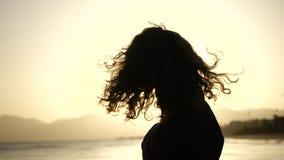 Конец замедленного движения вверх по силуэту молодой женщины двигая ее голову с волосами дуя в ветре смотря заход солнца над океа акции видеоматериалы