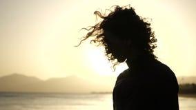 Конец замедленного движения вверх по силуэту молодой женщины двигая ее голову с волосами дуя в ветре смотря заход солнца над океа сток-видео