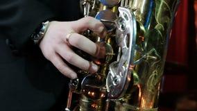 Конец ЗАМЕДЛЕННОГО ДВИЖЕНИЯ вверх человека играя на старом саксофоне Репетировать игрока джаза сток-видео