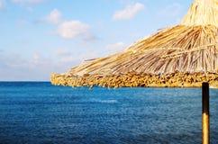 Конец зонтика пляжа соломы вверх с предпосылкой моря и неба Стоковое Изображение RF