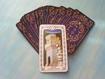 Конец карточек Tarot средневековый вверх с русским названием башня Tarot украшает на голубой деревянной предпосылке Стоковые Изображения