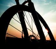 Конец колеса горного велосипеда вверх по съемке с небом захода солнца Стоковое Фото