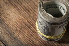 Конец крена доллара вверх на деревянном столе с космосом экземпляра Стоковые Фото