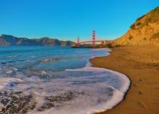 Конец моста золотых ворот вверх от пляжа хлебопека перед заходом солнца стоковое фото rf