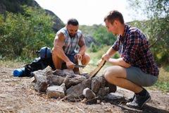Конец низкого угла вверх 2 молодых мужских туристов в древесине, организующ огонь лагеря для барбекю Один другого порции Стоковое Фото
