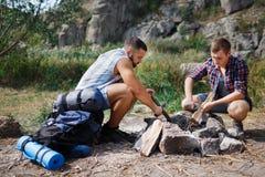 Конец низкого угла вверх 2 молодых мужских туристов в древесине, организующ огонь лагеря для барбекю Один другого порции Стоковые Фото