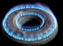 Конец огня пламени горелки газовой плиты вверх против черной предпосылки Стоковые Изображения