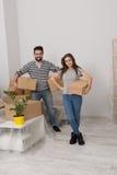 Конец положения excited молодых пар moving домашний вместе с коробками картона в их руках Стоковое фото RF