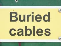 Конец предупредительного знака зарытых в землю кабелей вверх Стоковые Изображения