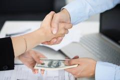 Конец рукопожатия женщины и человека вверх с деньгами в другом Хане стоковые изображения