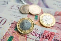 Конец финансовой предпосылки примечаний и монеток английского фунта вверх стоковые фото