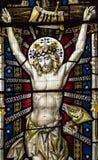 Конец цветного стекла церков Сент-Эндрюса вверх по Иисусу на кресте Стоковая Фотография
