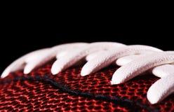 Конец шарика американского футбола вверх на черной предпосылке Стоковые Фото