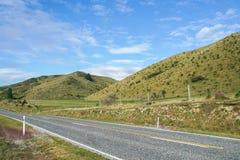 Конкретная дорога вдоль зеленого холма в пропуске Новой Зеландии Lindis с ясным голубым небом Стоковая Фотография RF