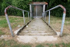 Конкретные шаги при частично заржаветые поручни металла водя к запертым дверям металла стоковое фото