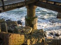 Конкретный штендер деревянной молы с утесами и волнами во время sunet стоковое изображение rf