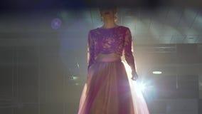 Конкурс красоты, шикарная женщина с кроной на головном и длинном платье идет вдоль этапа освещенного прожекторами видеоматериал