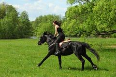Конноспортивная верховая лошадь девушки через лес весны Стоковые Изображения
